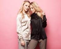 Δύο όμορφες νέες γυναίκες στα περιστασιακά ενδύματα που θέτουν πέρα από το ρόδινο υπόβαθρο Στοκ εικόνες με δικαίωμα ελεύθερης χρήσης