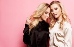 Δύο όμορφες νέες γυναίκες στα περιστασιακά ενδύματα που θέτουν πέρα από το ρόδινο υπόβαθρο στοκ εικόνες