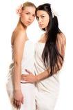 Δύο όμορφες νέες κυρίες με το τέλειο αγκάλιασμα δερμάτων, μπλε ματιών και λουλουδιών Στοκ Εικόνα