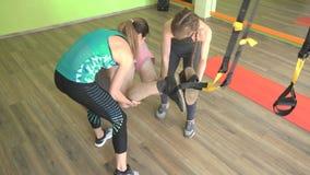 Δύο όμορφοι καυκάσιοι εκπαιδευτές κοριτσιών βοηθούν ένα παχύ άτομο για να κάνουν μια άσκηση στη γυμναστική στις αρθρώσεις TRX απόθεμα βίντεο