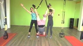 Δύο όμορφοι καυκάσιοι εκπαιδευτές κοριτσιών βοηθούν ένα παχύ άτομο για να κάνουν μια άσκηση στη γυμναστική στις αρθρώσεις TRX φιλμ μικρού μήκους