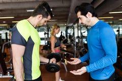 Δύο όμορφοι νεαροί άνδρες που κάνουν τη μυϊκή άσκηση στη γυμναστική Στοκ φωτογραφίες με δικαίωμα ελεύθερης χρήσης