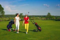 Δύο όμορφοι παίκτες γκολφ γυναικών που περπατούν στο γήπεδο του γκολφ Στοκ φωτογραφία με δικαίωμα ελεύθερης χρήσης