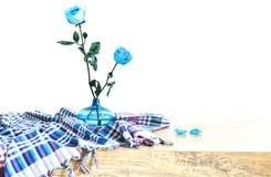Δύο όμορφος μπλε αυξήθηκε λουλούδια με τα πράσινα φύλλα σε ένα μπλε βάζο γυαλιού που διακοσμήθηκε με το ελεγμένο τραπεζομάντιλο κ στοκ φωτογραφία με δικαίωμα ελεύθερης χρήσης