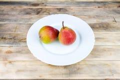 Δύο ώριμα αχλάδια στο άσπρο πιάτο στον αγροτικό ξύλινο πίνακα Στοκ Φωτογραφίες