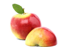 Δύο ώριμα κόκκινος-κίτρινα μήλα με ένα πράσινο φύλλο που απομονώνεται σε ένα άσπρο υπόβαθρο Ολόκληρο ένα μήλο και ένα μισό υγιές  Στοκ Εικόνες