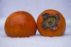 Δύο ώριμα πορτοκαλιά persimmons βρίσκονται στο χιόνι Στοκ εικόνα με δικαίωμα ελεύθερης χρήσης
