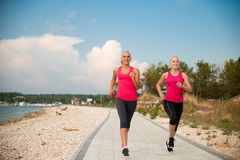 Δύο athlets γυναικών που τρέχουν στην παραλία - καλοκαίρι W ξημερωμάτων Στοκ Εικόνες