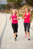 Δύο athlets γυναικών που τρέχουν στην παραλία - καλοκαίρι W ξημερωμάτων Στοκ Εικόνα