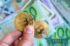 Δύο bitcoins στο τους παραδίδουν το δολάριο και τους ευρο- λογαριασμούς Investme Στοκ Εικόνες