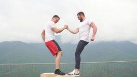 Δύο bodybuilders τινάζουν τα χέρια πρίν αρχίζουν το διπλό workout φιλμ μικρού μήκους