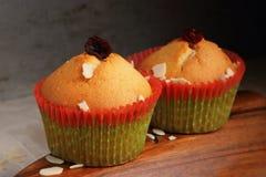 Δύο cupcakes στο έγγραφο του νέου έτους για ένα ξύλινο πιάτο στοκ εικόνες