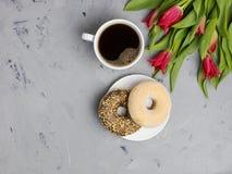 Δύο donuts και φλυτζάνι καφέ με τις τουλίπες Γκρίζο υπόβαθρο, τοπ άποψη, διάστημα για το κείμενο στοκ φωτογραφίες με δικαίωμα ελεύθερης χρήσης