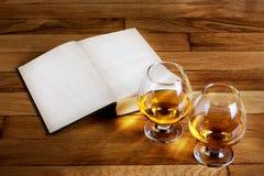 Δύο goblets του κονιάκ και του ανοικτού βιβλίου Στοκ εικόνα με δικαίωμα ελεύθερης χρήσης