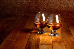 Δύο goblets του κονιάκ στην ξύλινη αντίθετη κορυφή Στοκ εικόνα με δικαίωμα ελεύθερης χρήσης