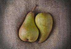 Δύο juicy αχλάδια που αγκαλιάζονται μαζί burlap ή hessian στοκ φωτογραφία
