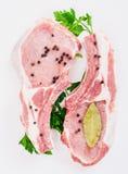 Δύο juicy κομμάτι του κρέατος στο κόκκαλο με ένα πιπέρι, ο μαϊντανός και το σκόρδο και το φύλλο κόλπων βρίσκονται στο άσπρο υπόβα Στοκ φωτογραφίες με δικαίωμα ελεύθερης χρήσης