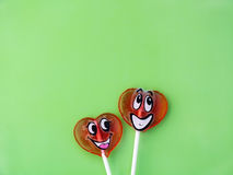 Δύο lollipops στο πράσινο υπόβαθρο άνδρας αγάπης φιλιών έννοιας στη γυναίκα Στοκ Εικόνες