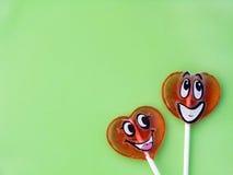 Δύο lollipops στο πράσινο υπόβαθρο άνδρας αγάπης φιλιών έννοιας στη γυναίκα στοκ φωτογραφίες