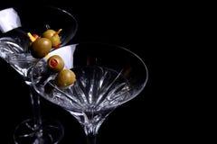 Δύο martini γυαλιά με τις ελιές στο Μαύρο Στοκ Εικόνες