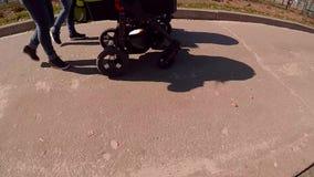 Δύο moms περπατούν με τον περιπατητή στο πάρκο απόθεμα βίντεο
