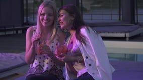 Δύο smilling κορίτσια που πίνουν τα κοκτέιλ σε ένα νυχτερινό κέντρο διασκέδασης Δύο φίλες κάθονται με τα κοκτέιλ και κουβεντιάζου απόθεμα βίντεο