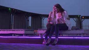 Δύο smilling φίλες που πίνουν τα κοκτέιλ σε ένα νυχτερινό κέντρο διασκέδασης Δύο κορίτσια κάθονται με τα κοκτέιλ και κουβεντιάζου φιλμ μικρού μήκους