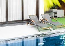 Δωμάτιο ξενοδοχείων πολυτελείας με τη λίμνη, χορτοτάπητα και δύο sunbeds. Στοκ Εικόνα
