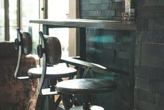 Δύο swirly υψηλές καρέκλες που τοποθετούνται στο πλαίσιο του μακριού ξύλινου πίνακα φραγμών στο lat στοκ εικόνες