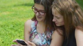 Δύο teengers κοριτσιών με το κινητό τηλέφωνο υπαίθριο απόθεμα βίντεο