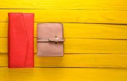 Δύο women& x27 πορτοφόλι του s σε ένα κίτρινο ξύλινο υπόβαθρο Εξαρτήματα τάσης διάστημα αντιγράφων Στοκ Εικόνες