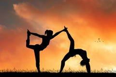 Δύο women do yoga θέτουν στην αυγή απεικόνιση αποθεμάτων