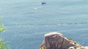Δύσκολη ακτή και μπλε τοπίο θαλάσσιου νερού Πλέοντας σκάφος στη θάλασσα και δύσκολος απότομος βράχος στο πράσινο νησί Μπλε θάλασσ φιλμ μικρού μήκους