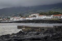 Δύσκολη ακτή λάβας με τα αρχικά άσπρα λιμενικά σπίτια στην ανατολή στο νησί Pico Στοκ Εικόνες