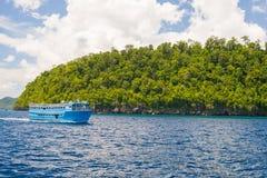 Δύσκολη ακτή του νησιού που επισημαίνεται από τα νησάκια και που καλύπτεται από την πυκνή πολύβλαστη πράσινη ζούγκλα στη ζωηρόχρω Στοκ Φωτογραφία