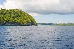 Δύσκολη ακτή του νησιού που επισημαίνεται από τα νησάκια και που καλύπτεται από την πυκνή πολύβλαστη πράσινη ζούγκλα στη ζωηρόχρω Στοκ φωτογραφία με δικαίωμα ελεύθερης χρήσης