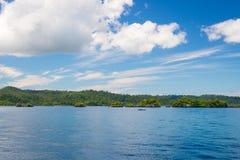 Δύσκολη ακτή του νησιού που επισημαίνεται από τα νησάκια και που καλύπτεται από την πυκνή πολύβλαστη πράσινη ζούγκλα στη ζωηρόχρω Στοκ εικόνες με δικαίωμα ελεύθερης χρήσης