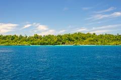 Δύσκολη ακτή του νησιού που επισημαίνεται από τα νησάκια και που καλύπτεται από την πυκνή πολύβλαστη πράσινη ζούγκλα στη ζωηρόχρω Στοκ Εικόνες