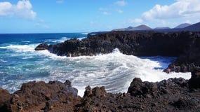 Δύσκολη ακτή Los Hervideros με τον κυματιστό ωκεανό και ηφαίστεια στο υπόβαθρο, Lanzarote, Κανάρια νησιά, Ισπανία Στοκ εικόνες με δικαίωμα ελεύθερης χρήσης