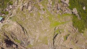 Δύσκολος απότομος βράχος άποψης κηφήνων και μπλε θαλάσσιο νερό Εναέριος φάρος τοπίων στα πράσινα σκάφη απότομων βράχων ANS βουνών φιλμ μικρού μήκους