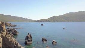 Δύσκολος απότομος βράχος και πλέοντας βάρκα κατά την μπλε άποψη κηφήνων θαλάσσιου νερού άνωθεν Απότομος βράχος βουνών και σκάφος  απόθεμα βίντεο