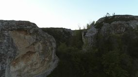 Δύσκολος απότομος βράχος πέρα από την πράσινη κοιλάδα και τη μικρή σκηνή πλάνο Γραφικό τοπίο του τεράστιου δύσκολου λόφου φιλμ μικρού μήκους