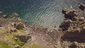 Δύσκολος απότομος βράχος στην ακτή και την μπλε άποψη κηφήνων θάλασσας Τοπ βουνό απότομων βράχων άποψης και τυρκουάζ ωκεάνιο νερό απόθεμα βίντεο