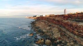 Δύσκολος σκόπελος της ακτής πλάνο Τοπ άποψη της ακτής των δύσκολων απότομων βράχων ακτών του κοκκίνου με τις τρύπες και τις κολλώ απόθεμα βίντεο