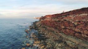 Δύσκολος σκόπελος της ακτής πλάνο Τοπ άποψη της ακτής των δύσκολων απότομων βράχων ακτών του κοκκίνου με τις τρύπες και τις κολλώ φιλμ μικρού μήκους