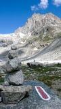 Δύσκολο τοπίο βουνών με τις αιχμές βουνών και τον τύμβο και τον κόκκινο και άσπρο δείκτη ιχνών Στοκ Εικόνες