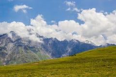 Δύσκολα βουνά Καύκασου στην περιοχή Kazbeki με το νεφελώδη μπλε ουρανό Στοκ Φωτογραφίες