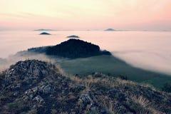 Δύσκολη αιχμή βασαλτών στο λόφο Δασικό σύνολο κοιλάδων της ευγενών ομίχλης και του ήλιου επάνω από τη βαριά υδρονέφωση Στοκ εικόνα με δικαίωμα ελεύθερης χρήσης
