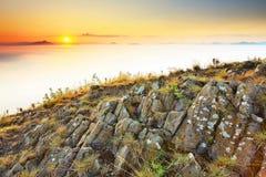 Δύσκολη αιχμή βασαλτών στο λόφο Δασικό σύνολο κοιλάδων της ευγενών ομίχλης και του ήλιου επάνω από τη βαριά υδρονέφωση Στοκ Φωτογραφίες