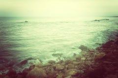 Δύσκολη ακτή και θυελλώδης θάλασσα στην πράσινη πυράκτωση Στοκ Φωτογραφία